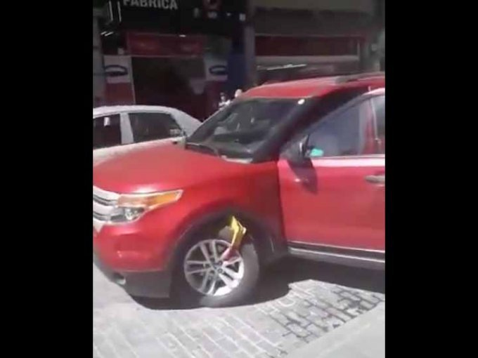La conductora de una Ford Explorer, prefirió avanzar con todo e inmovilizador, antes que pagar. Foto: Twitter